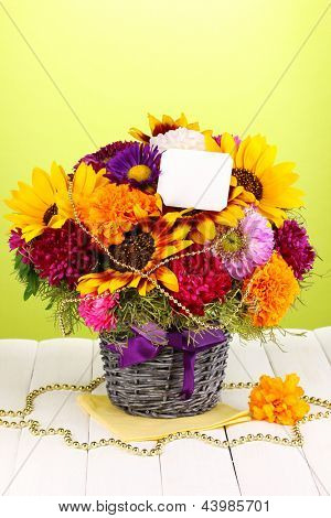 Beautiful bouquet of bright flowers with paper note on wooden table on green background