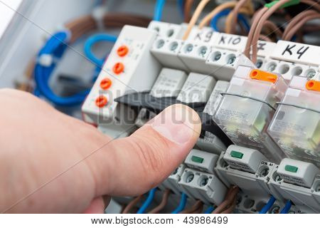 Hand of an electrician turning on a fusebox