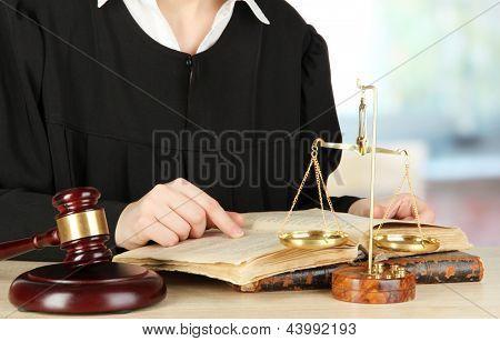 Juiz sentado à mesa durante audiência no fundo da sala