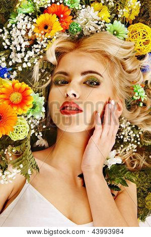 Woman with flower hairstyle lying on grass. Art photo.