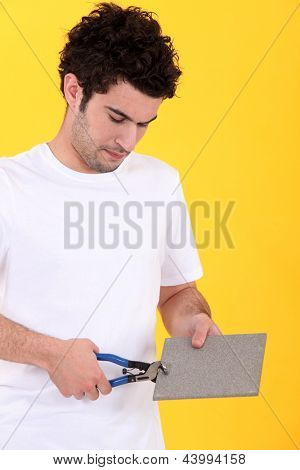 young tiler at work against yellow studio background
