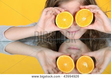 Girl with orange halves in front of her eyes