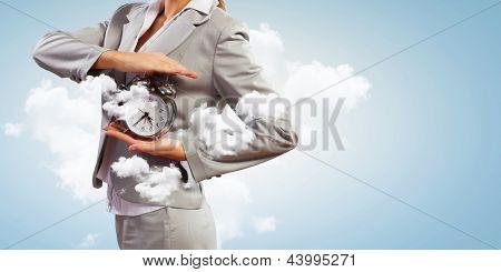 Imagen de la joven empresaria sosteniendo alarmclock contra fondo nublado