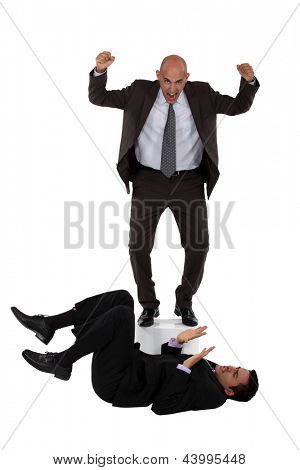 Angry boss shouting at employee laying on the floor