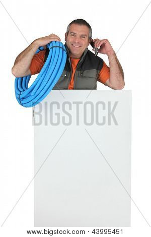 Electrician with roll of blue corrugated plastic tubing, a phone and a board left blank for your message