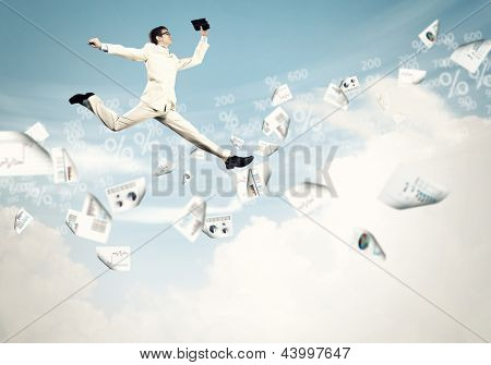Image of a businessman jumping high against financial background
