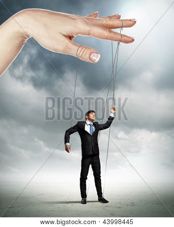 Businessman marionette on ropes controlled by puppeteer