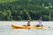 Young couple waving and rowing kayak on river summer vacation