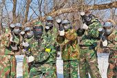 stock photo of air paint gun  - seven friends in masks and camouflage play paintball in the fresh air outdoor - JPG
