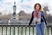 Woman smiles and leans on railing at background of monument to Alfonso XII near pond in Retiro Park