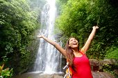 stock photo of hawaiian girl  - Hawaii woman tourist excited by waterfall during travel on the famous road to Hana on Maui - JPG