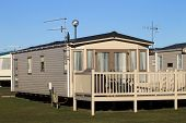 picture of trailer park  - Scenic view of trailers in caravan park with blue sky background - JPG
