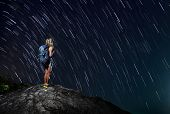 stock photo of meteoric rain  - Hiker with backpack standing on top of a mountain with star trails on the background  - JPG