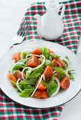 image of snow peas  - Fresh snow peas and tomato salad on plate vertical