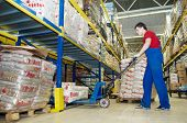 pic of food truck  - worker with fork pallet truck stacker in warehouse loading Group of food packages - JPG