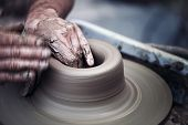 stock photo of molding clay  - Hands working on pottery wheel  - JPG