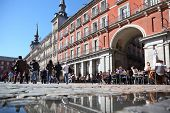 MADRID - MARCH 9: Tourists walk and sit at tables in cafe at Plaza Mayor on March 9 2012 in Madrid,