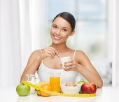 stock photo of breakfast  - young woman with healthy breakfast and measuring tape - JPG