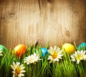 Easter. Colorful Easter Painted Eggs in Spring Grass and Flowers over Wooden Background.