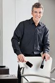 Environmental portrait of happy male hairdresser holding straightener and brush at salon