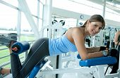 image of derriere  - woman at the gym doing exercises on a machine for her bottom - JPG