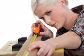 image of workbench  - Woman measuring the length of a plank of wood - JPG