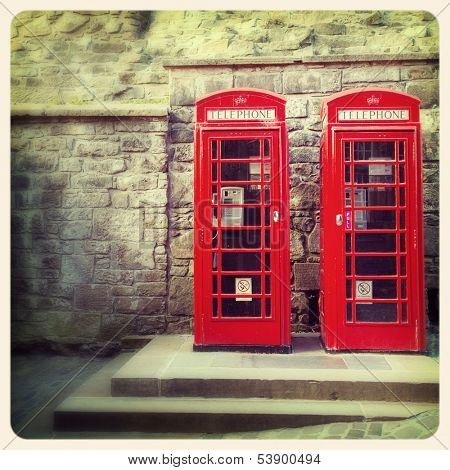 A pair of traditional British red phone boxes against the wall of Edinburgh Castle, Scotland. Cross processed to look like and aged instant photo.