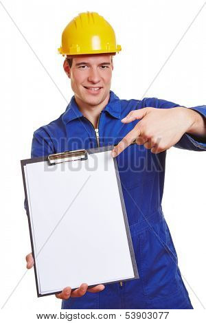 Construction worker with helmet and jump suit pointing to empty clipboard