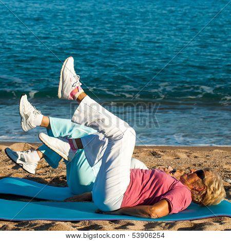 Senior Women Doing Leg Exercises On Beach.