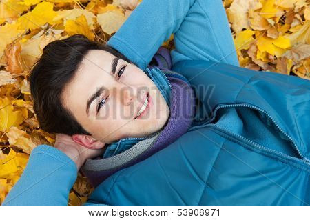 Young smiling man portrait laying in foliage in autumn park.