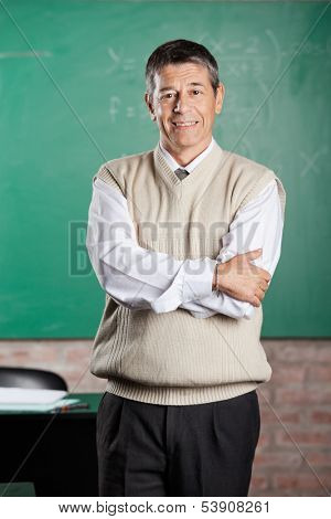 Portrait of confident male professor standing arms crossed in classroom