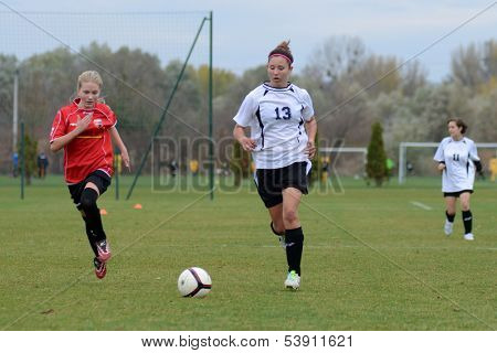 KAPOSVAR, HUNGARY - NOVEMBER 3: Kata Recsei (white 13) in action at Hungarian Championship under 15 women soccer game Rakoczi FC (white) vs Pecsi MFC (red) November 3, 2013 in Kaposvar, Hungary.