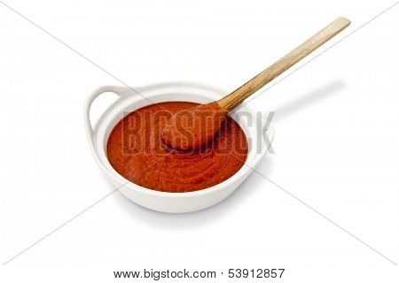 Tomato sauce in a bowl with wooden spoon on white background