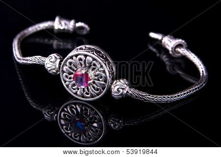 Silver bracelet with on black background.