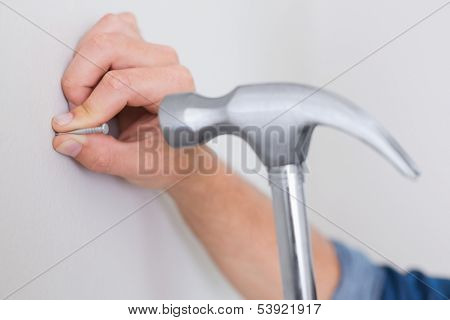 Extreme Close up of a handyman hammering nail in wall