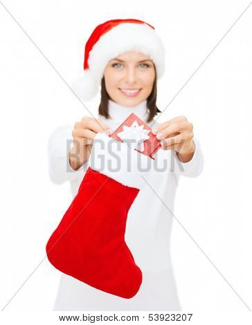 christmas, x-mas, winter and happiness concept - smiling woman in santa helper hat with small gift box and stocking