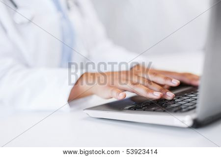 office, health, medicine, technology and internet concept - female doctor using her laptop computer