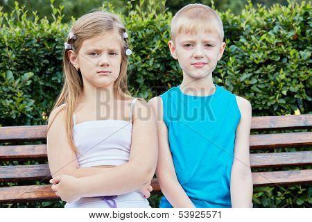 Two children sit on bench in summer park