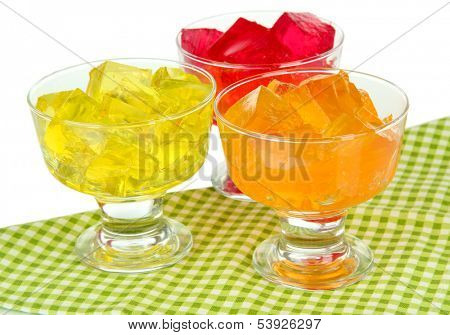 Tasty jelly cubes in bowls on table on white background