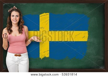 Beautiful And Smiling Woman Showing Flag Of Sweden On Blackboard