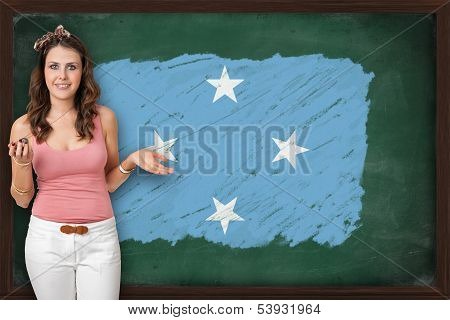 Beautiful And Smiling Woman Showing Flag Of Micronesia On Blackboard