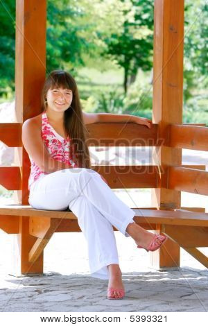 Attractive Girl Sitting On Wooden Bench In Park