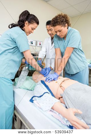 Medical team performing CPR on dummy patient in hospital room