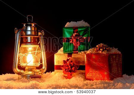 Gift wrapped Christmas presents on snow illuminated by the glow from an oil lantern, black background.