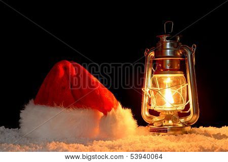 A Santa Claus or Father Christmas hat on snow illuminated by the glow of an oil filled lantern, black background.