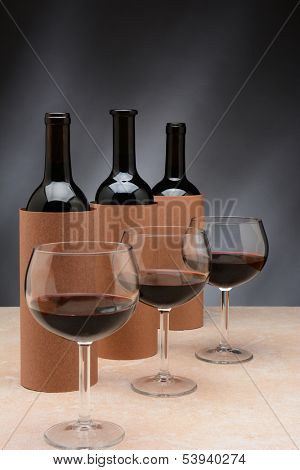 Three different wine bottles and wine glasses set up for a blind wine tasting. The bottles are covered by blank cylinders to hide the label. Wine glasses are partially filled with red wine.