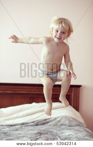 Portrait of a 2 years old child jumping on his parent's bed