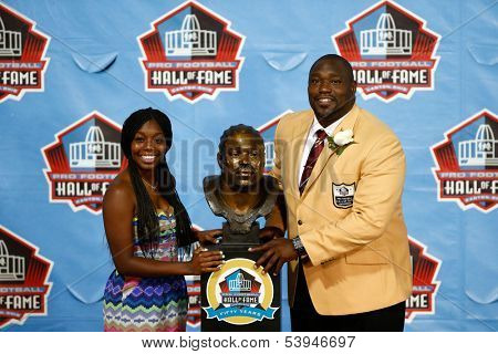 CANTON, OH-AUG 3: Mercedes Sapp (L) and her father defensive tackle Warren Sapp pose with his bust at the NFL Class of 2013 Enshrinement Ceremony at Fawcett Stadium on August 3, 2013 in Canton, Ohio.