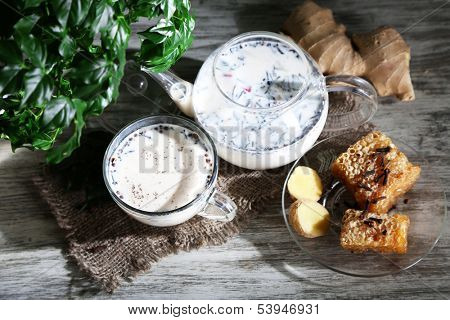 Teapot and cup of tea with milk and spices on sackcloth of wooden table