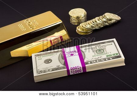 Gold coins and a gold bar with a pile of American cash for use as any investment or transactional inference.